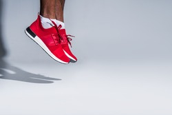 cropped shot of young african american sportsman in sneakers jumping on grey