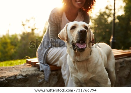 Cropped shot of young african lady wearing white costume walking with pretty dog in park