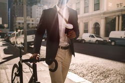 Cropped shot of young businessman going to work by bike. Man in suit holding a cup of coffee walking by the street with his bicycle.