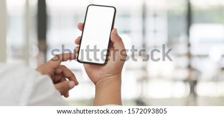 Cropped shot of young businessman using his blank screen smartphone with blurred office background