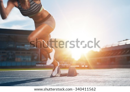 Cropped shot of young female athlete launching off the start line in a race. Female runner started the sprint from the starting line with bright sunlight.