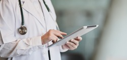 Cropped shot of young female doctor summarises patient charts with digital tablet in her office room