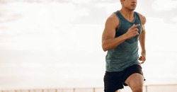 Cropped shot of young man running along a seaside promenade. Healthy young male runner working out on a road by the sea.