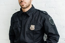 cropped shot of young policeman in front of white brick wall