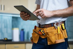 Cropped shot of young repairman wearing a tool belt with various tools using digital tablet while standing indoors