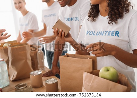 cropped shot of young volunteers group packing food and drinks for charity Сток-фото ©