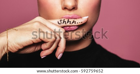 Cropped shot of young woman biting finger with shhh word. Young woman placing finger on lips asking shh against pink background. #592759652