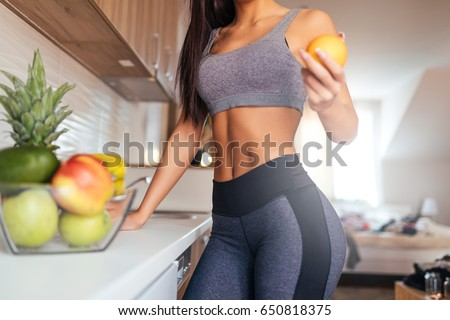 Stock Photo Cropped shot of young woman eating fruit for breakfast.