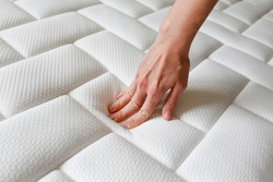 Cropped shot of young woman's hand testing white orthopedic mattress on firmness. Female pressing hypoallergenic foam mattress surface to check its softness. Close up, copy space, top view, background