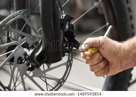 Cropped shot view of a man's hand working in bicycle repair shop, worker repairing modern bike brakes using special tool