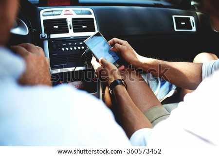 Cropped shot view of a young man using navigation on mobile phone while sitting on front seat in luxury car cabriolet, male viewing location map in network via cell telephone during road trip