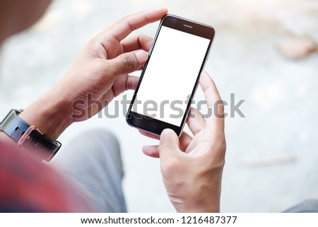 Cropped shot view of man hands holding smart phone with blank copy space screen for your text message or information content, female reading text message on cell telephone during in urban setting. #1216487377