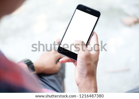 Cropped shot view of man hands holding smart phone with blank copy space screen for your text message or information content, female reading text message on cell telephone during in urban setting. #1216487380