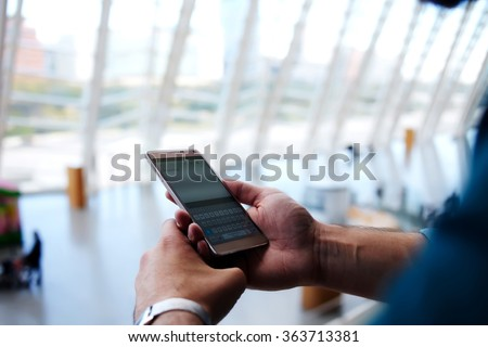 Cropped shot view of man\'s hands orders electronic ticket via mobile phone application during summer trip, young male reading text message on cell telephone while standing in waiting hall of airport