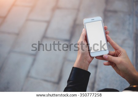 Cropped shot view of woman's hands holding smart phone with blank copy space screen for your text message or information content, female reading text message on cell telephone during in urban setting #350777258