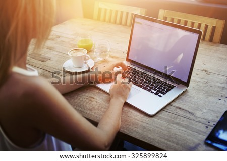 Cropped shot view of young woman keyboarding on laptop computer with blank copy space screen while sitting in cafe, blonde female student working on net-book after her lectures in University,flare sun