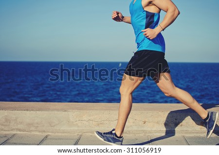 Cropped shot with muscular build man running along the seashore with copy space area for your text message or advertising content, male jogger working out outdoors o the beach at sunny afternoon Foto stock ©
