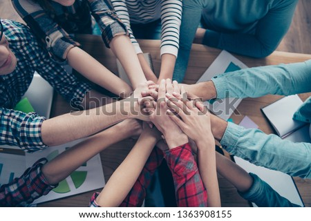 Cropped top above high angle view of company executive staff wearing casual putting palms together motivation over table desk at workplace workstation indoors