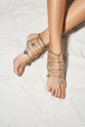 Cropped top view shot of girl's crossed legs isolated on the sandy background. The lady with light brown pedicure is wearing a silver anklet with coins and chains. Voguish women's summer accessory.