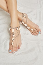 Cropped top view shot of woman's crossed legs on the sandy background. The girl with powder blue pedicure is wearing a silver anklet adorned with chains and shells. Trendy women's summer accessory.