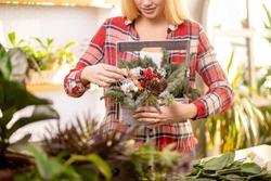 cropped unrecognizable florist woman with blonde hair holding wonderful composition of plants, wearing red casual shirt