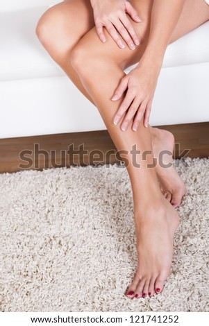 Cropped view image of a young woman stroking her bare shapely legs with her hands after waxing them