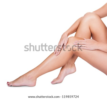 Cropped view image of the hands of woman sitting caressing her bare silky smooth sexy legs isolated on white