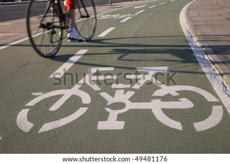 Cropped view of a bicyclist going the wrong way on a two-way bicycle path. Horizontal shot.