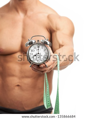 Cropped view of a muscular young man holding clock and measuring tape. It is high time for workout concept.