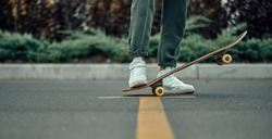 Cropped view of a stylish man in white sneakers and green pants with a skateboard, on a yellow crosswalk.