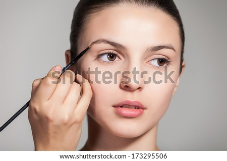 Cropped view of a young woman having brow color added to her eyebrows
