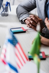 cropped view of african american businessman sitting with clenched hands near digital translator with uae flag emblem, blurred foreground