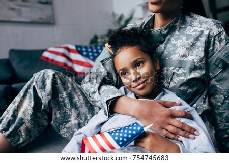 cropped view of african american daughter and female soldier in military uniform with american flag at home