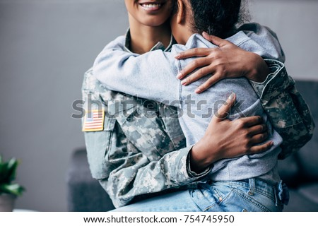 cropped view of african american daughter hugging mother in military uniform at home