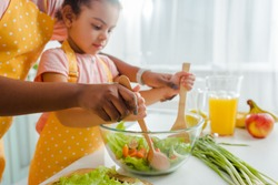 cropped view of african american mother and child mixing fresh salad