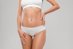 cropped view of beautiful slim woman in underwear posing with hand on hip isolated on grey