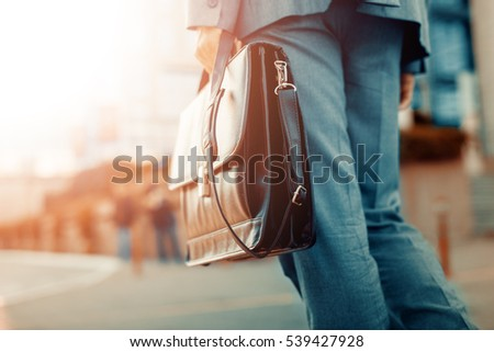 Cropped view of businessman holding a briefcase outdoors