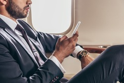 cropped view of businessman in suit using smartphone in private plane