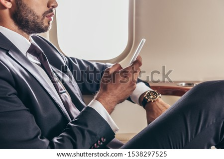 cropped view of businessman in suit using smartphone in private plane  Photo stock ©