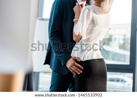 cropped view of businessman touching buttocks of coworker in office