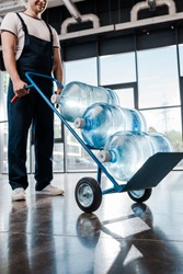 cropped view of cheerful delivery man in uniform holding hand truck with bottled water