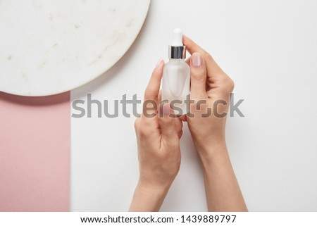 cropped view of cropped view of woman holding cosmetic glass bottle near plate on white pink surface #1439889797