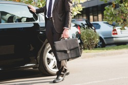 cropped view of diplomat standing with briefcase near car