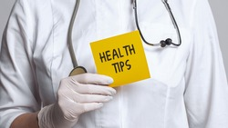 Cropped view of doctor in a white coat and sterile gloves holding a note with words - Health Tips. Medical concept