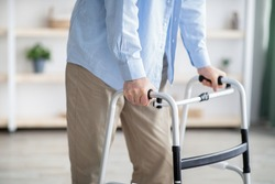 Cropped view of elderly man walking with frame at home, closeup. Unrecognizable senior male using medical equipment to move around his house. Disabled older person in need of professional help