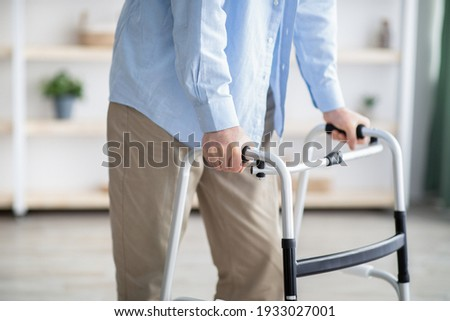 Cropped view of elderly man walking with frame at home, closeup. Unrecognizable senior male using medical equipment to move around his house. Disabled older person in need of professional help Photo stock ©