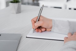 Cropped view of freelancer writing on notebook near laptop on table