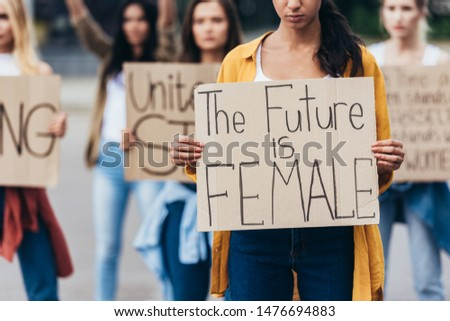 cropped view of girl holding placard with inscription the future is female near feminists on street #1476694883