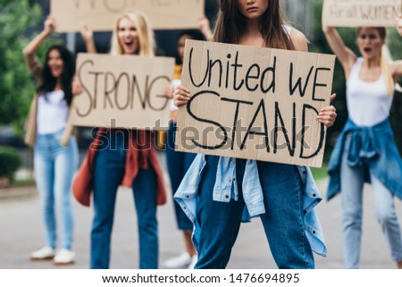 cropped view of girl holding placard with inscription united we stand near feminists on street #1476694895