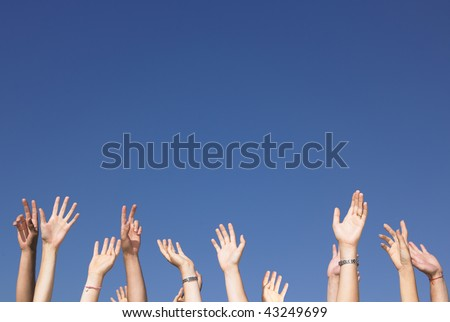 Cropped view of group of people with arms raised against a blue sky. Horizontally framed shot.